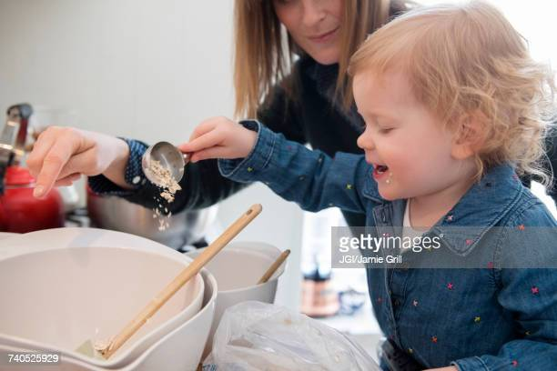 Caucasian girl cooking with mother in kitchen