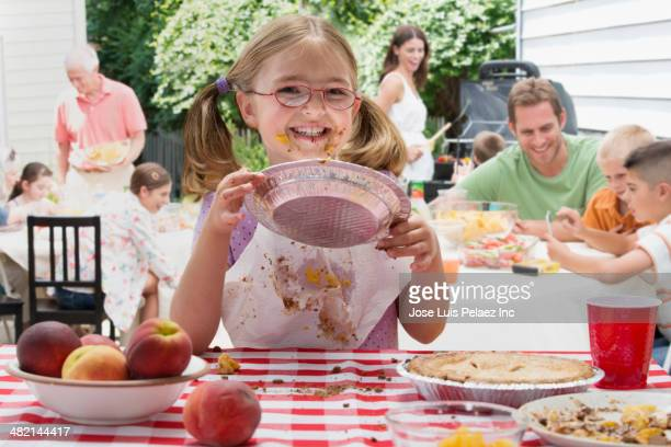 Caucasian girl covered in pie at picnic