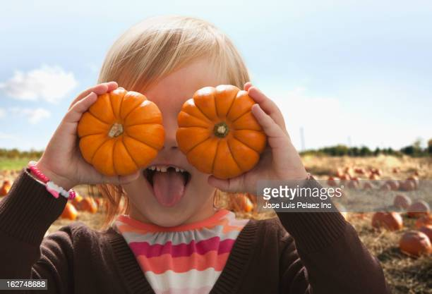Caucasian girl covering eyes with small pumpkins