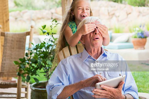 Caucasian girl covering grandfather's eyes on patio