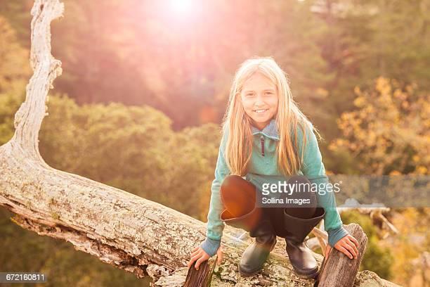 Caucasian girl crouching on log