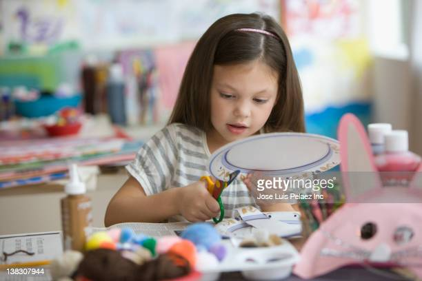Caucasian girl cutting paper plate with scissors