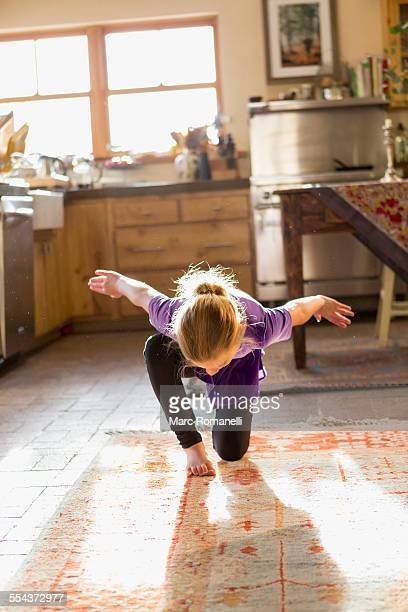 Caucasian girl dancing in kitchen