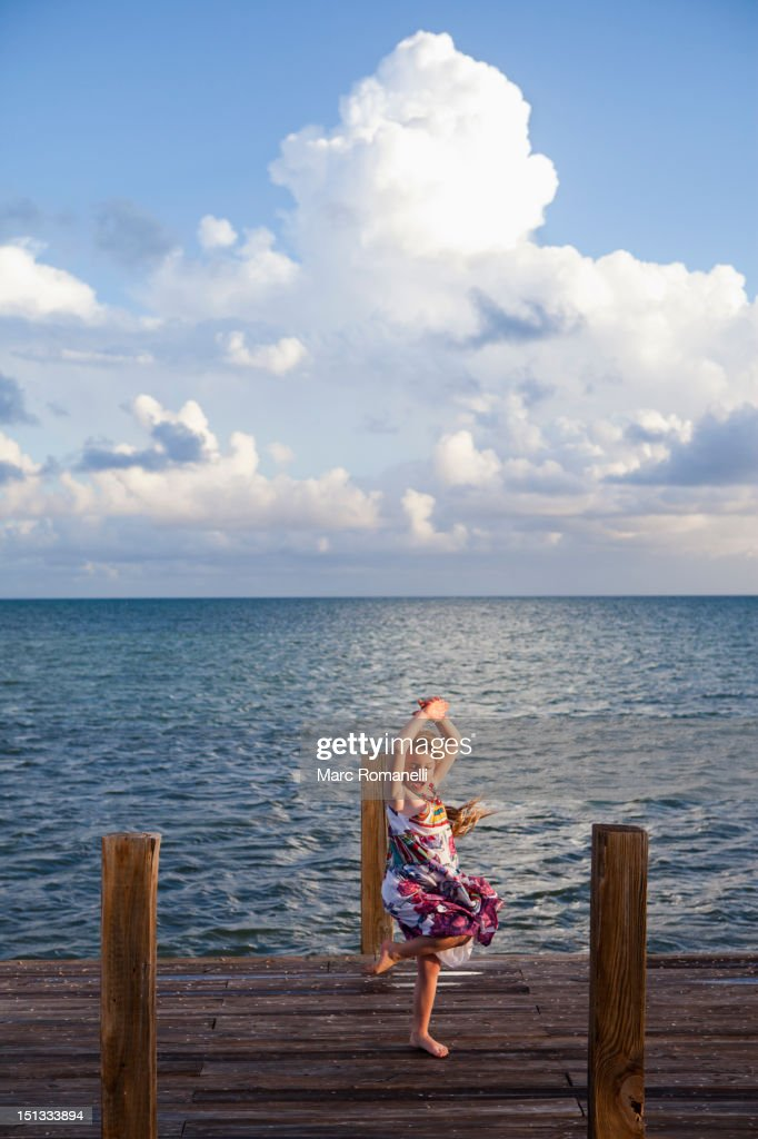 Caucasian girl dancing on pier : Stock Photo