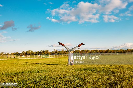Caucasian girl doing headstand in field on ranch
