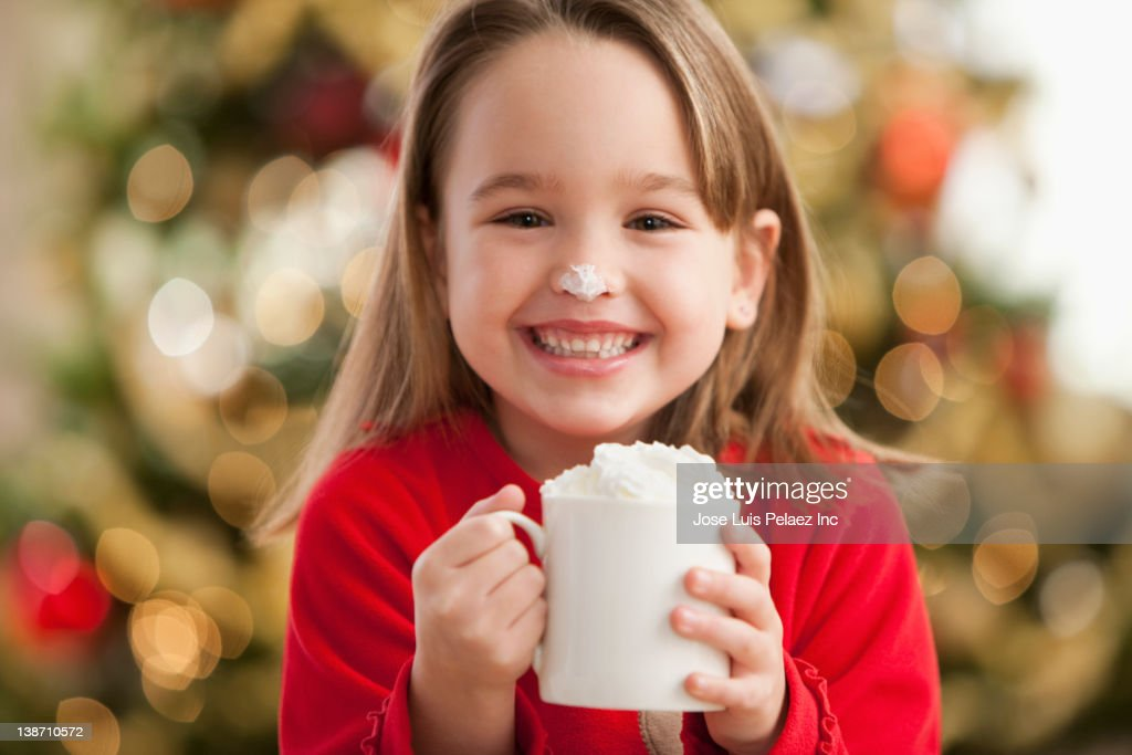 Caucasian girl drinking hot chocolate at Christmastime : Stock Photo