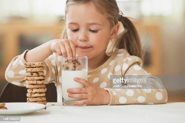 Caucasian girl dunking cookies in milk