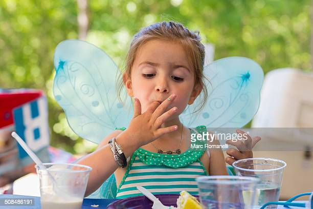 Caucasian girl eating cake at birthday party