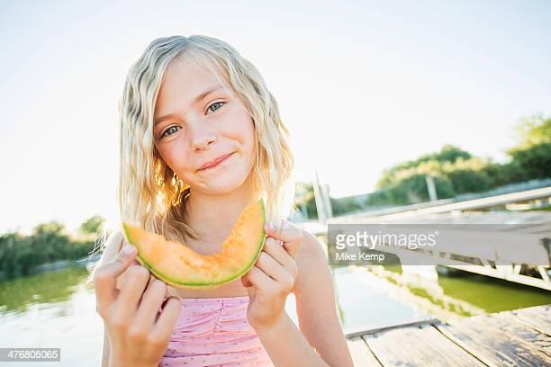Caucasian girl eating cantaloupe slice
