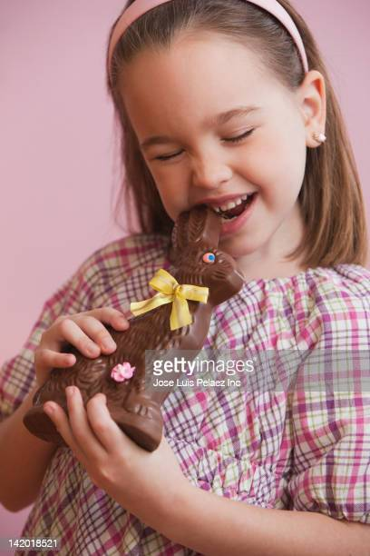 Caucasian girl eating chocolate Easter bunny