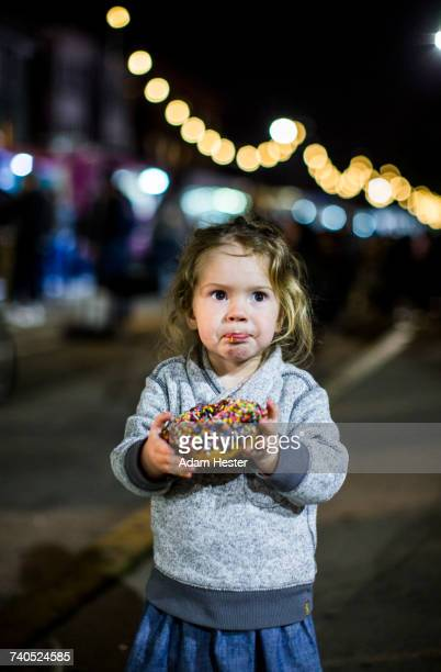 Caucasian girl eating donut outdoors at night