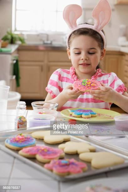 Caucasian girl eating Easter cookies in kitchen