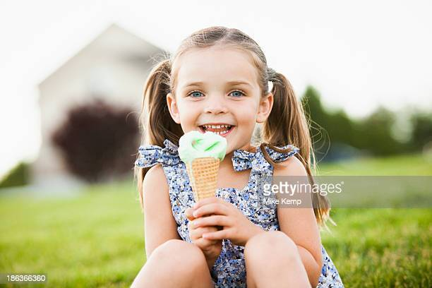 Caucasian girl eating ice cream outdoors