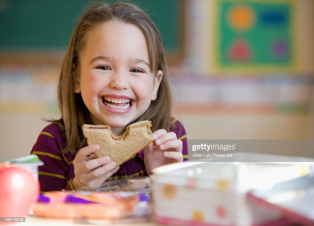Caucasian girl eating lunch in classroom