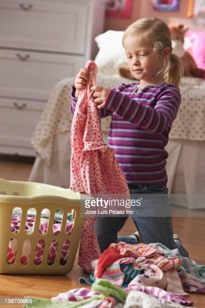 Caucasian girl folding laundry