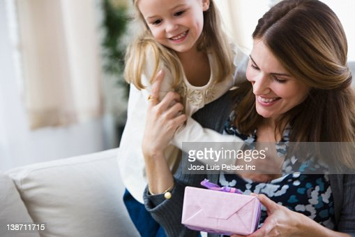 Caucasian girl giving birthday gift to mother