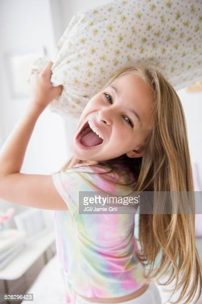 Caucasian girl having pillow fight in bedroom