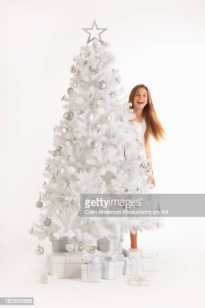 Caucasian girl hiding behind Christmas tree