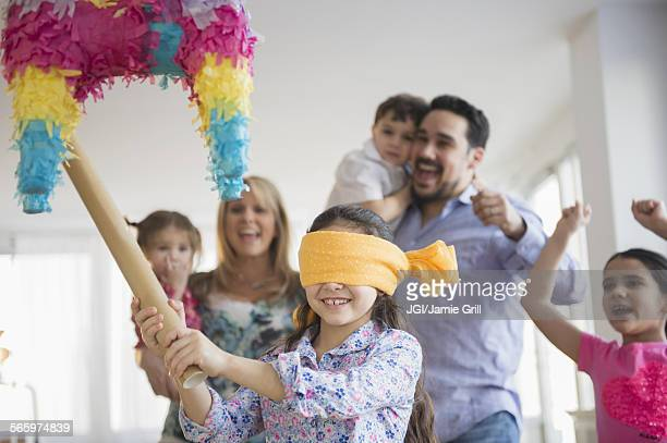 Caucasian girl hitting pinata at birthday party