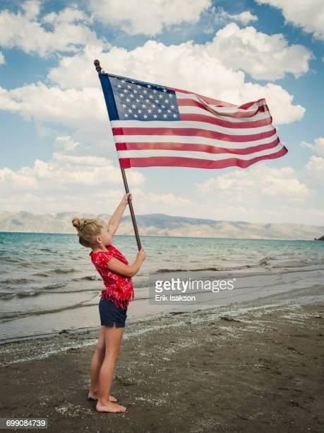 Caucasian girl holding American flag at beach