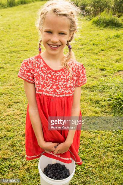 Caucasian girl holding basket of blueberries