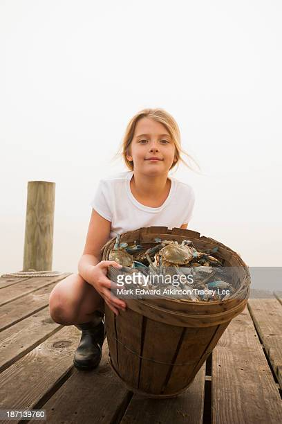 Caucasian girl holding basket of crabs
