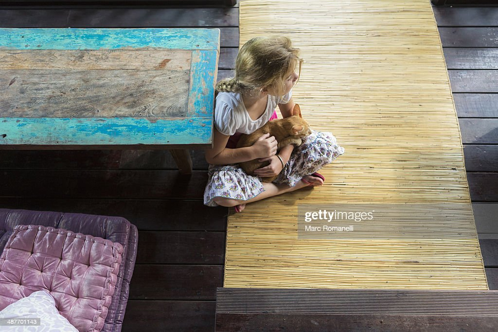 Caucasian girl holding cat on patio : Stock Photo