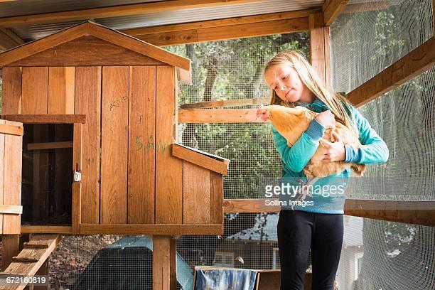 Caucasian girl holding chicken in chicken coop