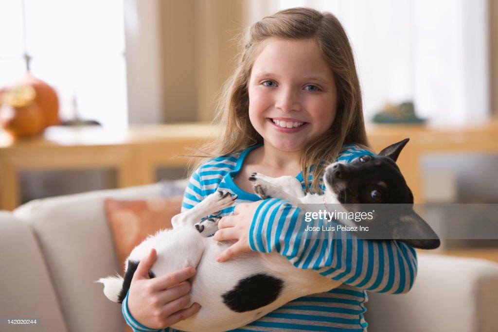 Caucasian girl holding dog : Stock Photo