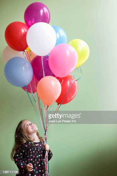 Caucasian girl holding floating balloons