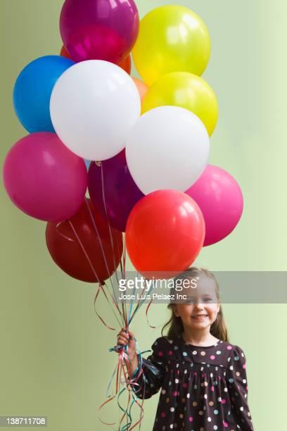 Caucasian girl holding floating balloons