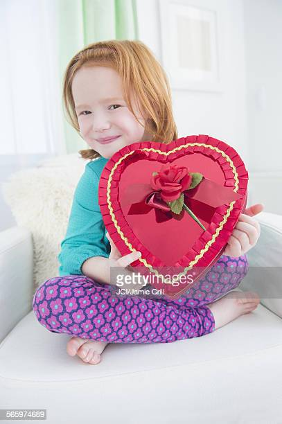 Caucasian girl holding gift box of candy