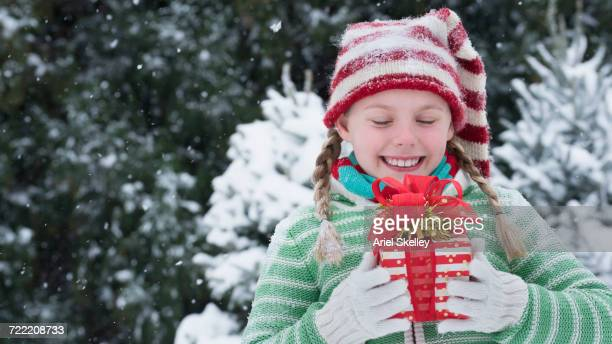 Caucasian girl holding gift box outdoors in winter