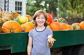 Caucasian girl holding miniature gourd at pumpkin patch