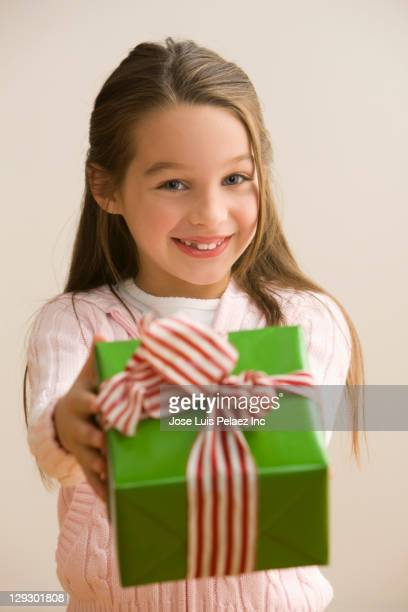 Caucasian girl holding out Christmas gift