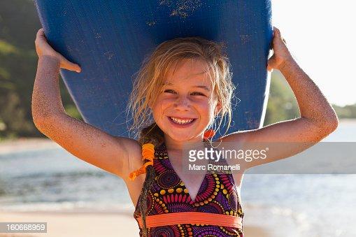 Caucasian girl holding paddle board : Stock Photo
