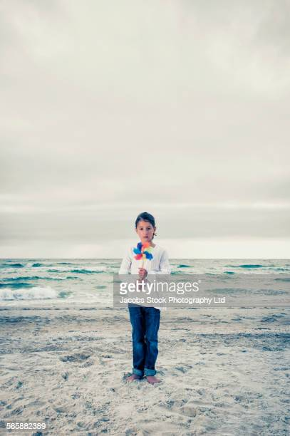 Caucasian girl holding pinwheel on beach