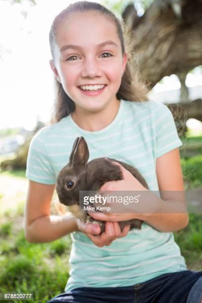 Caucasian girl holding rabbit