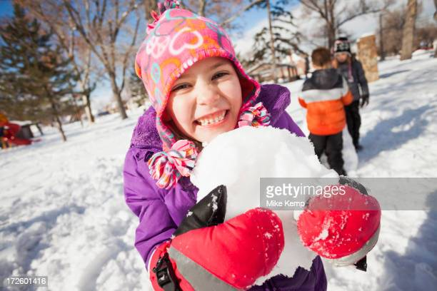 Caucasian girl holding snowball outdoors