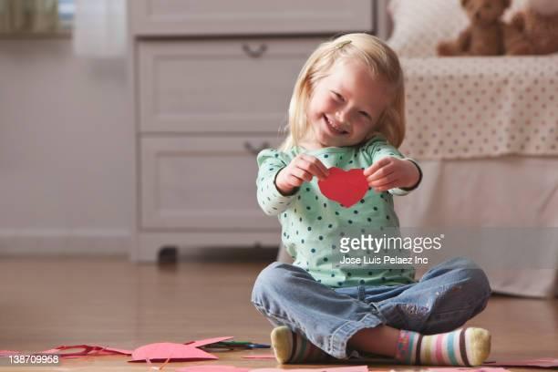 Caucasian girl holding Valentine heart