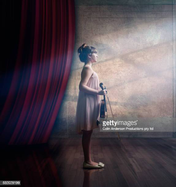 Caucasian girl holding violin on stage