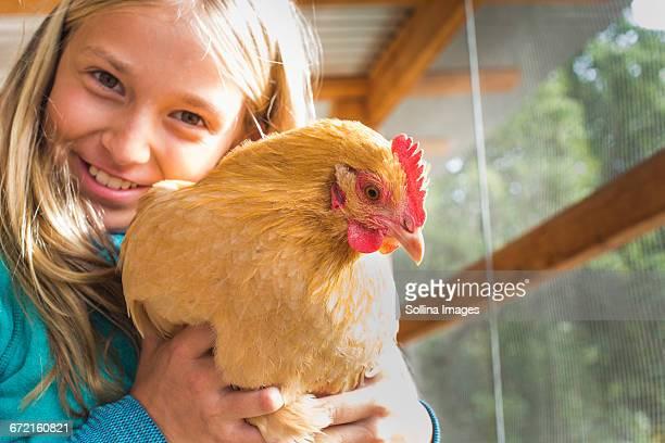 Caucasian girl hugging chicken in chicken coop