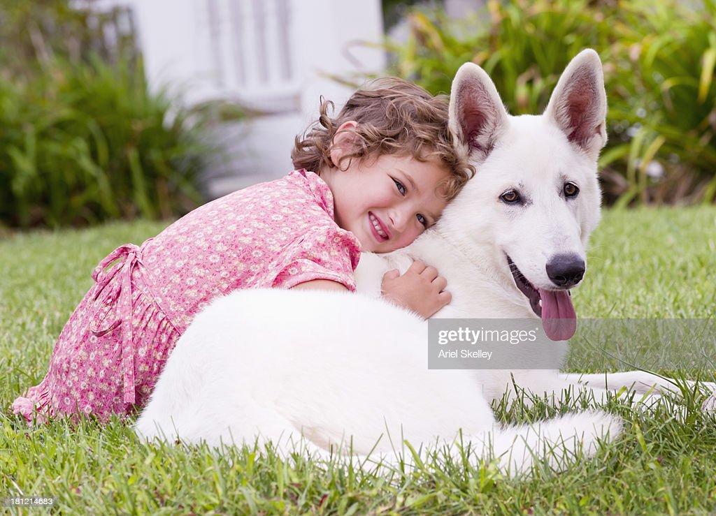 Caucasian girl hugging dog in backyard : Stock Photo