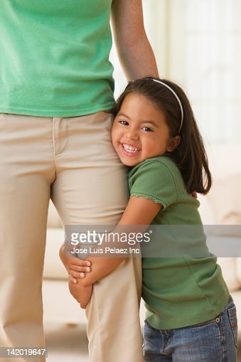 Caucasian girl hugging mother's leg : Stock Photo