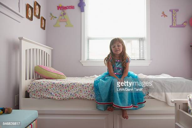 Caucasian girl in princess costume sitting on bed