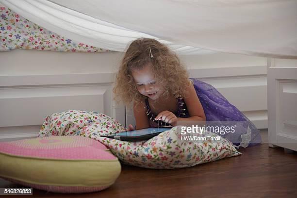 Caucasian girl in princess costume using digital tablet in blanket fort