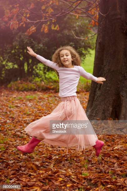 Caucasian girl jumping for joy in autumn leaves