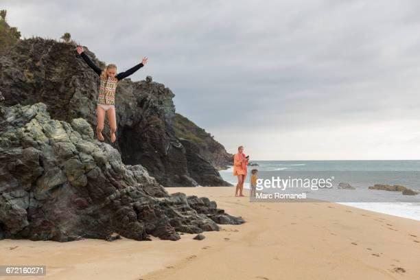 Caucasian girl jumping off rocks at beach