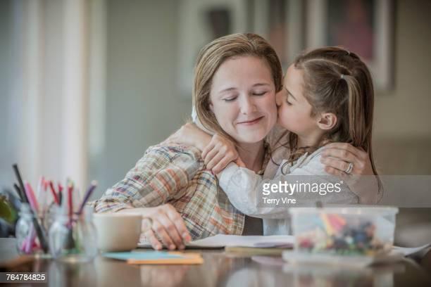 Caucasian girl kissing cheek of mother