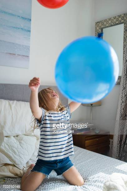 Caucasian girl kneeling on bed playing with balloons